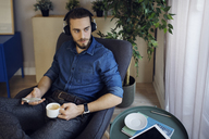 Man holding coffee cup and mobile phone listening music while sitting on chair at home - CAVF45018