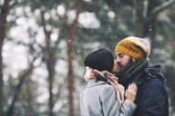 Romantic couple kissing while standing in forest during winter - CAVF45225