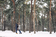 Happy couple looking at each other while standing on snowy field in forest - CAVF45234
