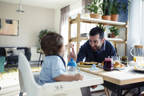 Happy father playing with son while having breakfast at home - CAVF45243