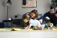 Parents and son playing with toy train at home - CAVF45246