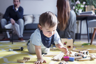 Boy playing with toy train while parents in background - CAVF45249