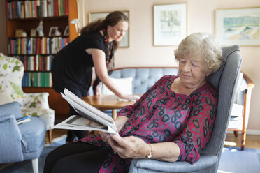Senior woman reading newspaper while granddaughter cleaning in background - MASF06484