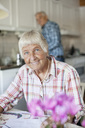Portrait of smiling senior woman with man in background - MASF06511