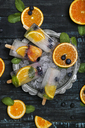Homemade detox popsicles with blueberries, orange slices and mint leaves on black wood - RTBF01165