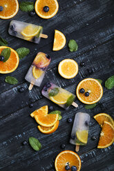 Homemade detox popsicles with blueberries, orange slices and mint leaves on black wood - RTBF01168