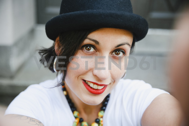 Portrait of smiling woman with hat taking selfie - RTBF01172