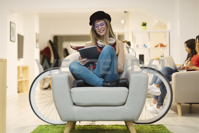 Casual young woman using tablet in coworking space - OCAF00215