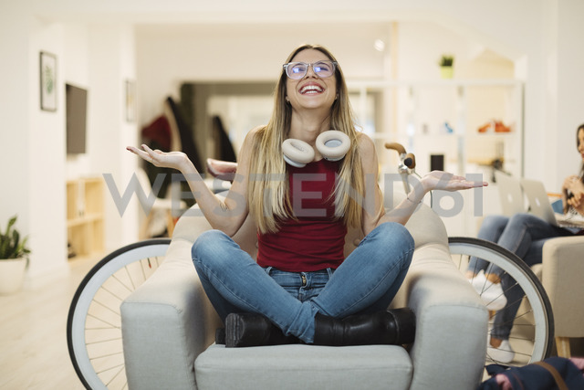 Happy casual young woman sitting in armchair in coworking space - OCAF00218