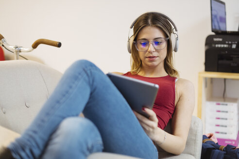 Casual young woman with headphones using tablet in coworking space - OCAF00221