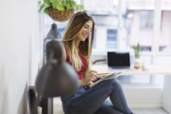 Smiling casual young woman taking notes in the office - OCAF00230