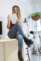 Smiling casual young woman sitting on desk in the office taking notes - OCAF00233