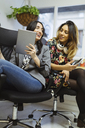 Two happy young women talking in the office - OCAF00236
