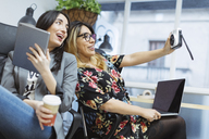 Two happy young women in the office taking a selfie - OCAF00239