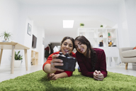 Two happy young women lying on the floor in coworking space taking a selfie - OCAF00245