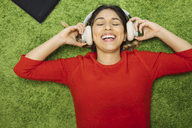 Happy young woman lying on carpet listening to music with headphones - OCAF00248