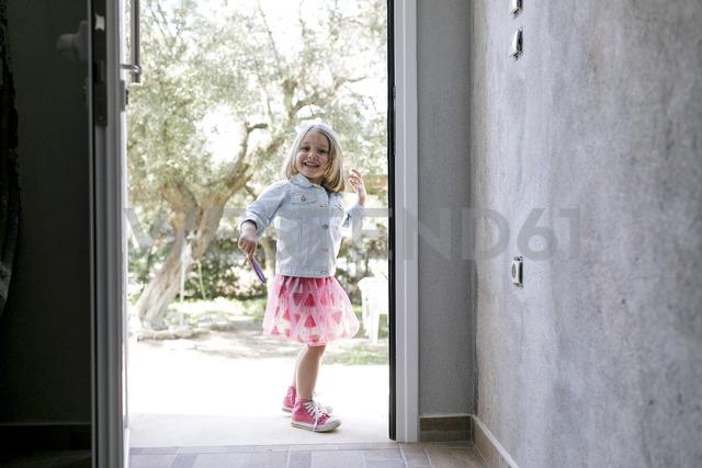 Portrait of laughing little girl standing in front of open entry door - KMKF00211