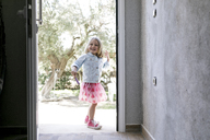 Portrait of laughing little girl standing in front of open entry door - KMKF00211