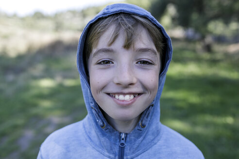 Portrait of laughing boy wearing blue hooded jacket - KMKF00214