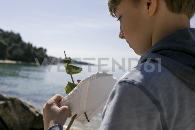 Boy with self-made toy boat in front of the sea - KMKF00217 - Katharina Mikhrin/Westend61