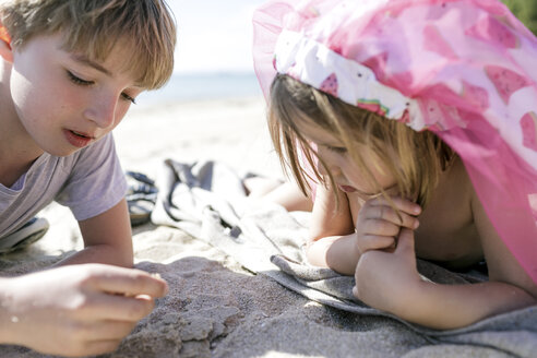 Boy and his little sister lying on the beach - KMKF00226