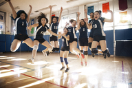 Happy female volleyball team jumping at court - CAVF45285
