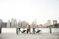 Couple embracing while standing by bicycles against East river in city - CAVF45375