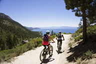 Rear view of cyclists riding bicycles on dirt road against clear blue sky - CAVF45384