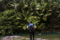 Rear view of woman with backpack standing at lakeshore in El Yunque National Forest - CAVF45387