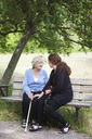 Grandmother and grand daughter sitting together on park bench - MASF06568