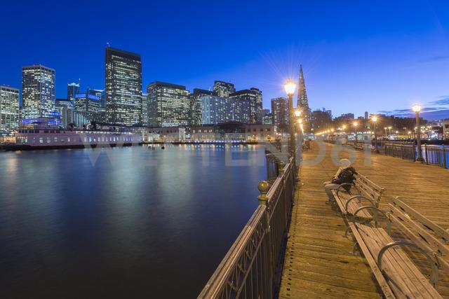USA, California, San Francisco, Pier 7, woman sitting on bench at blue hour - MKFF00360