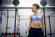 Thoughtful female athlete standing at gym - CAVF45474