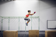 Side view of confident female athlete doing box jumping at gym - CAVF45498