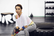 Portrait of confident female athlete sitting on tire at gym - CAVF45513