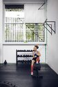 Thoughtful female athlete sitting on bench at gym - CAVF45516