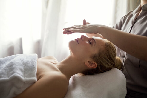 Midsection of therapist giving Reiki treatment to woman on face at spa - CAVF45579