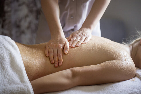 Midsection of female therapist massaging woman's back in spa - CAVF45585