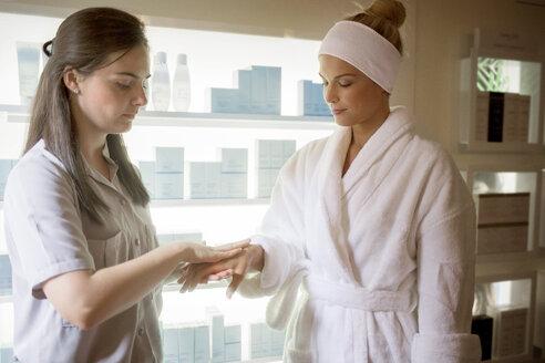 Massage therapist applying medicine on woman's hand in spa - CAVF45591
