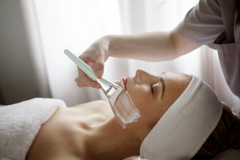 Midsection of therapist applying facial mask on woman in spa - CAVF45594