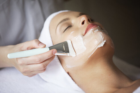 Female therapist applying facial mask on woman's face in spa - CAVF45597