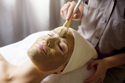 Therapist applying facial mask on woman's face in spa - CAVF45603