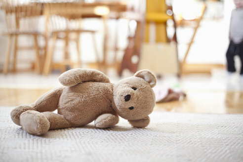 Abandoned teddy bear lying on carpet in house - MASF06617