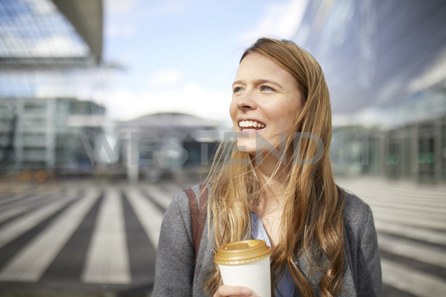 Portrait of smiling young businesswoman with coffee to go - PNEF00613