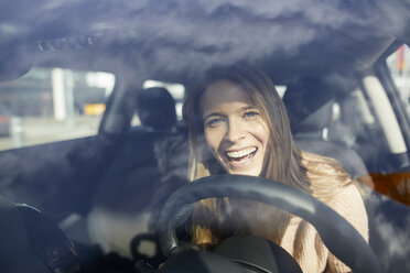Portrait of laughing young woman in car - PNEF00616