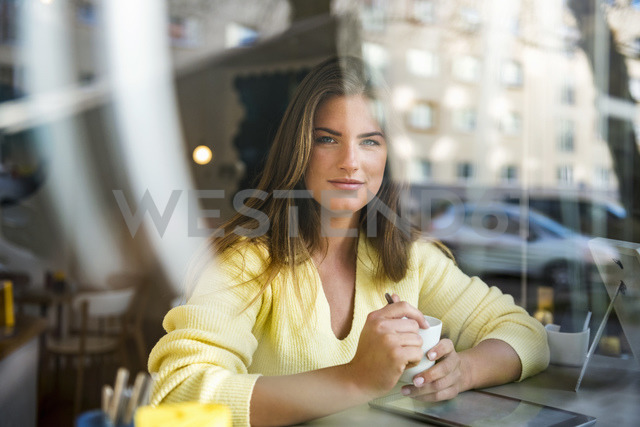 Portrait of smiling young woman in a cafe - DIGF03917