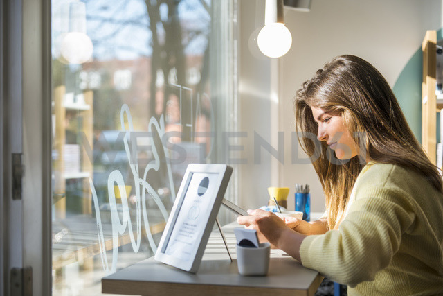 Young woman using tablet in a cafe - DIGF03920 - Daniel Ingold/Westend61