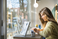 Young woman using tablet in a cafe - DIGF03920