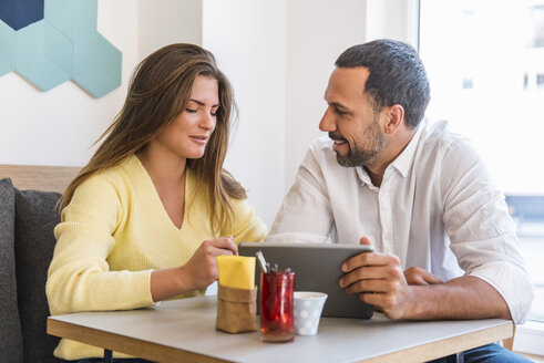 Young woman and man sharing tablet in a cafe - DIGF03923