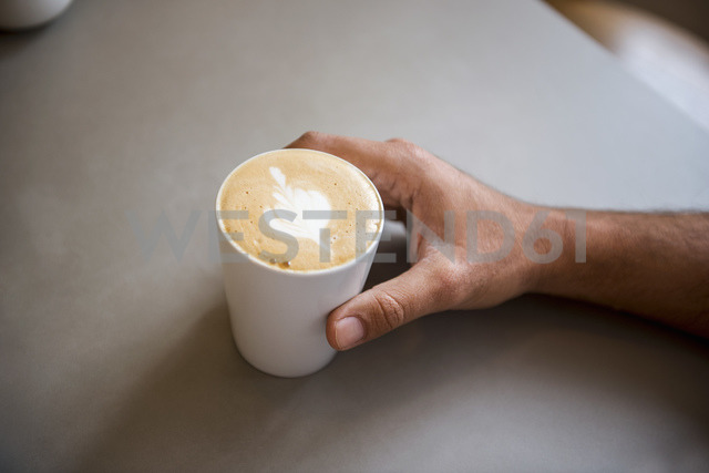 Hand and cup of cappuccino in a cafe - DIGF03926