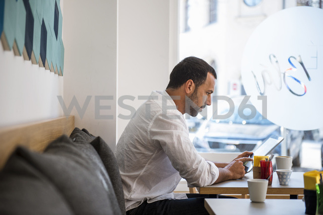 Man using tablet in a cafe - DIGF03932